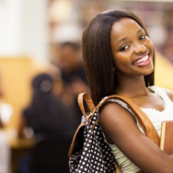 black female student sideways view smiling carrying books wearing backpack
