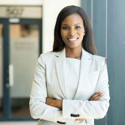 black woman standing witha rms folded looking confident outside business building