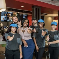 Colin and her employees pose in the lobby of McDonald's