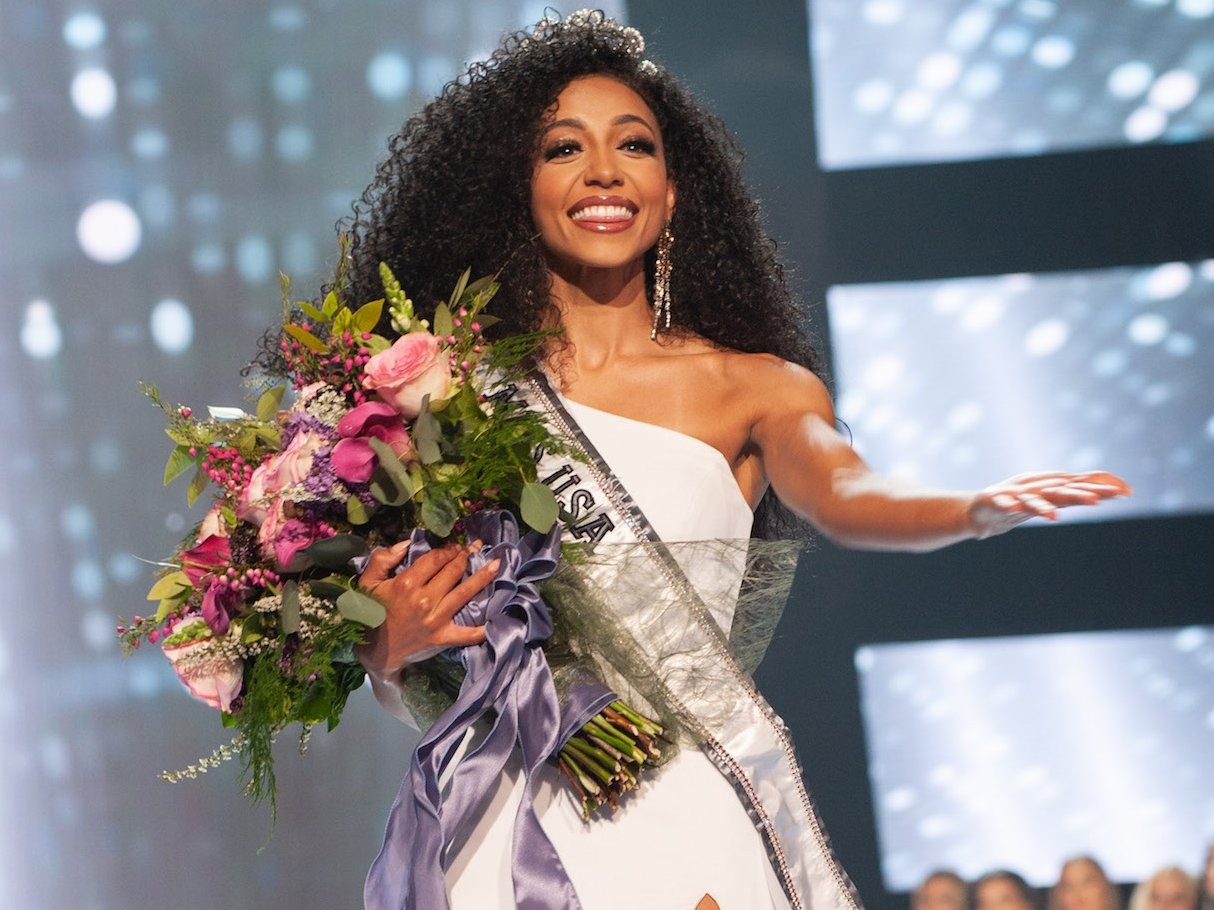 Chelsie Kryst miss usa winner standing on stage holding bouquest of flowers