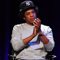 Jay-Z is seated in front of audience clapping his hands wearing a NYN baseball cap