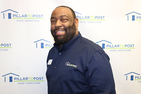 Kareem Mincey standing in front of home inspection logo background wearing his uniform