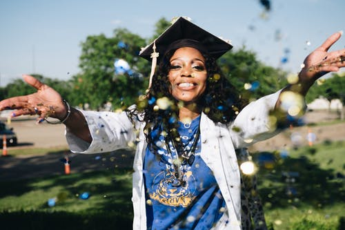 black woman college graduate outside with graduation cap on smiling
