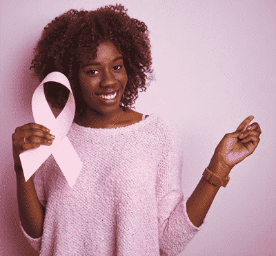 woman dressed in pink holding a pink ribbon for breast cancer awareness month