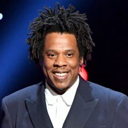 JAY-Z in blue suit and white collared suit on stage before performance