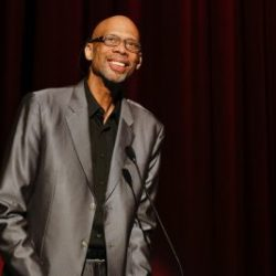 Kareem Abdul-Jabbar on a stage dressed in a suit smiling
