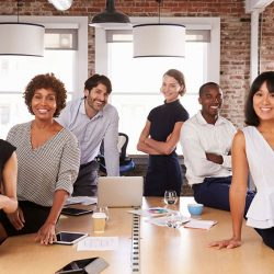 group of diverse co-workers gathered around conference table with laptops