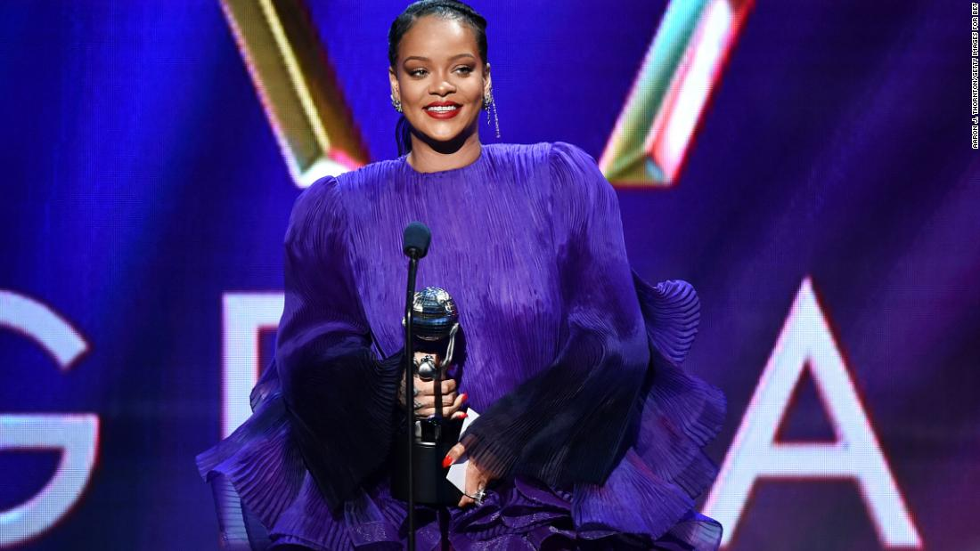 Rihanna, dresed in a floy purple dress, accepts her award on stage at the NAACP Image Awards ceremony