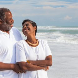 African American man and woman in retirement couple looking at each other on a deserted tropical beach