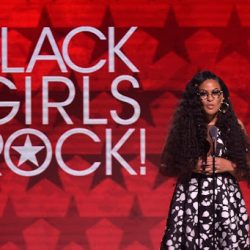everly Bond stands in front of large Black Girls Rock red promo background Black Girls Rock