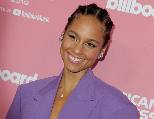 Alicia Keys smiling in front of Billboard Music background