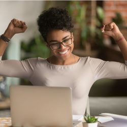 Black professional woman with hands up and excited looking at computer monitor while in Zoom meeting