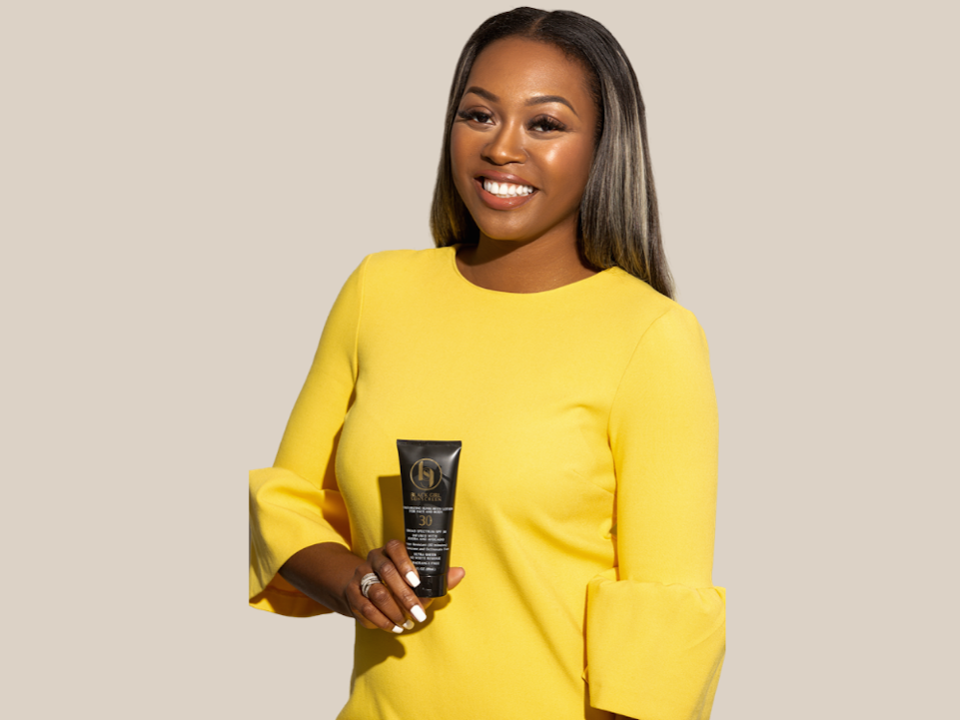 Shontay Lundy holding a bottle of Black Girl Sunscreen