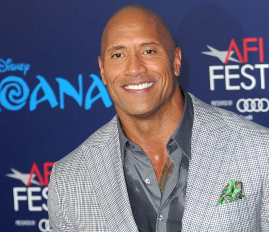 The Rock pictured smiling wearing a suit at a premiere event