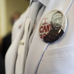 """button that reads """"I can't breathe"""" adorns the jacket of a mourner before the private funeral for George Floyd at The Fountain of Praise church"""