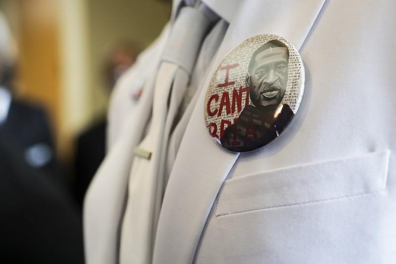 "button that reads ""I can't breathe"" adorns the jacket of a mourner before the private funeral for George Floyd at The Fountain of Praise church"