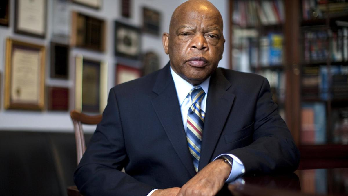 John Robert Lewis seated behind desk with books on a shelf in the background