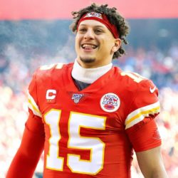 Patrick Mahomes on football wearing the red #15 jersey smiling
