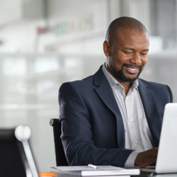 black businessman working from home during pandemic on laptop wearing a suit smiling