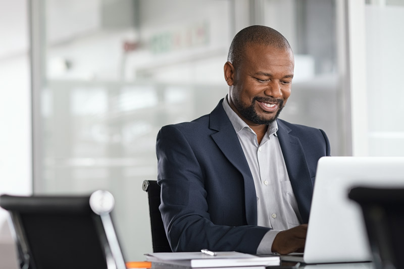 black businessman working on laptop wearing a suit smiling