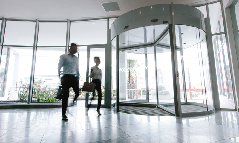 Motion blurred shot of two business people talking through modern office hallway. People walking in office entrance hall.