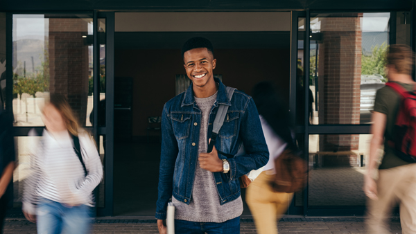 Portrait of african teenage boy at college campus with students walking by in motion blur. Happy young guy standing with his backpack looking at camera and smiling.