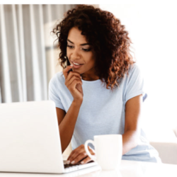 woman looking at laptop with coffee cup on table