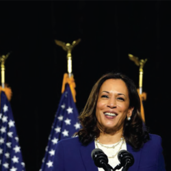 Kamala Harrsie stands behind podium smiling with U.S. flags in the background