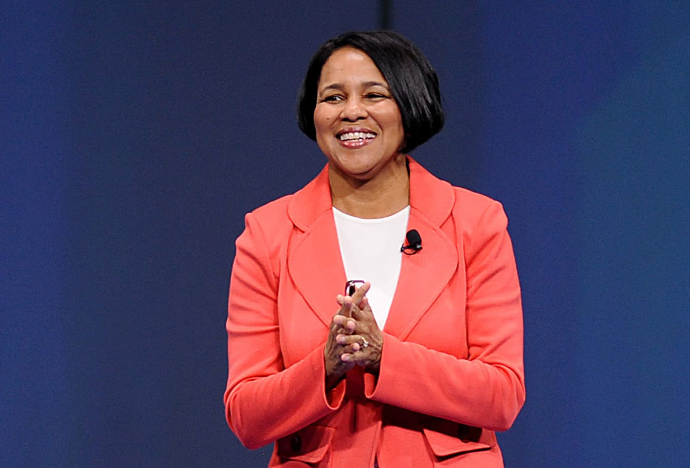 Rosalind Brewer standing on stage clapping hands smiling warmly to audience