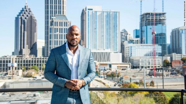 Jeezy wearing a blue suit with a skyline in the background