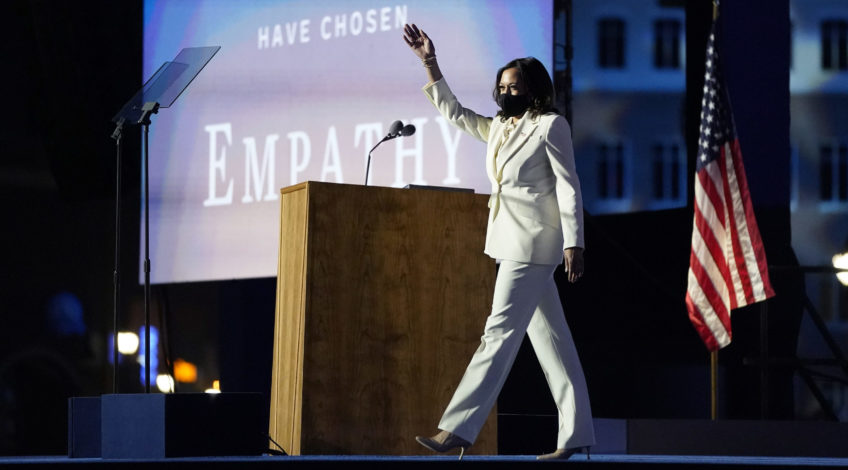 Kamala Harris on stage white suit wearing a mask