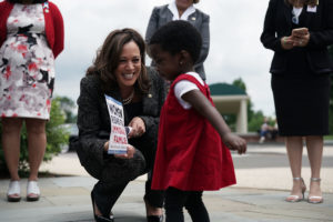 Kamala Harris with a girl in a red dress
