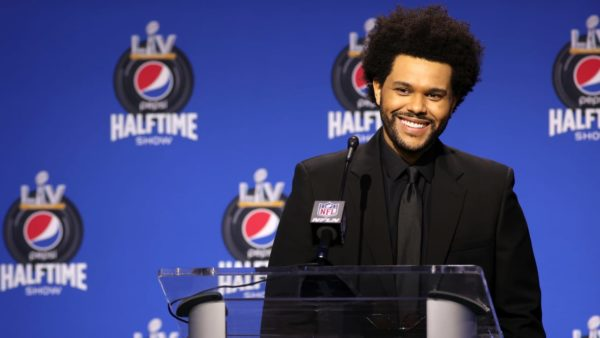 The Weekend giving a speach wearing black suit and tie for super bowl halftime show