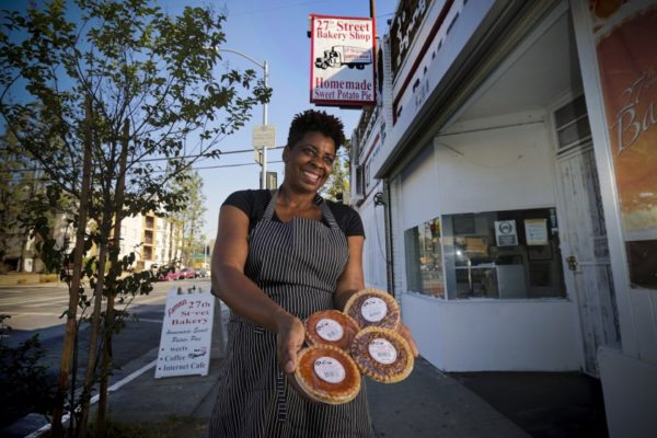 Black woman outside of her shop holding pies for super bowl