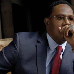 Master P posing with his hand over his mouth, wearing a suit and glasses