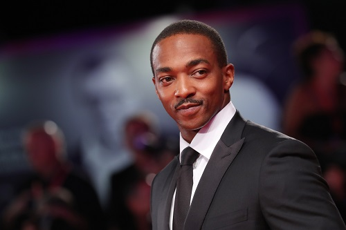 Anthony Mackie looking off in the distance in a press photo for a red carpet event