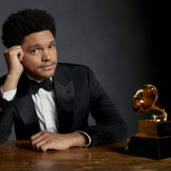 Trevor Noah poses with his head resting on his hand with a Grammy award in a tuxedo