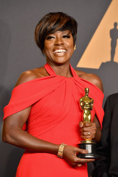 Viola Davis holding her award from the Oscars while wearing a red off the shoulder dress smiling