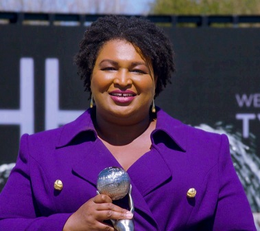Stacey Abrams up close in purple holding microphone