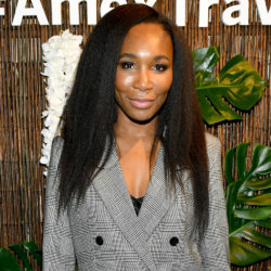 Venus williams wearing a gray suit jacket smiling at the camera