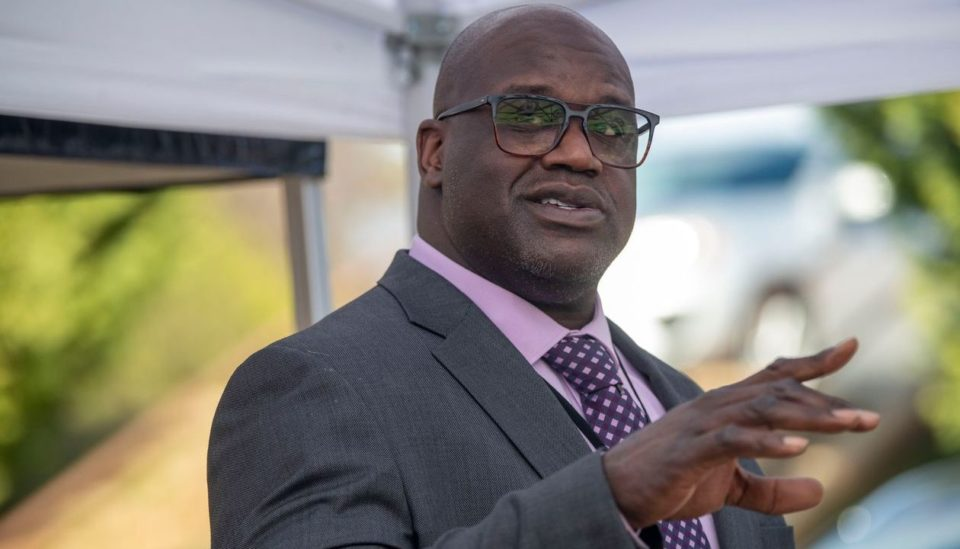 Shaquille O'Neil looking off to his right with his hand pointed forward speaking and wearing a suit and tie