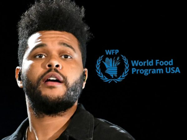 A headshot of the weeknd from a concert of his with the WFP logo next to him