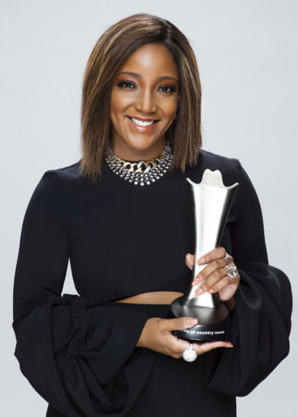 Mickey Guyton wearing a long sleeve black gown smiling at the camera and holding up her country music award