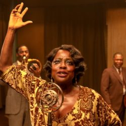 "Viola Davis as Ma Rainey in ""Ma Rainey's Black Bottom"" standing in front of a microphone with her right arm in the air while she sings"