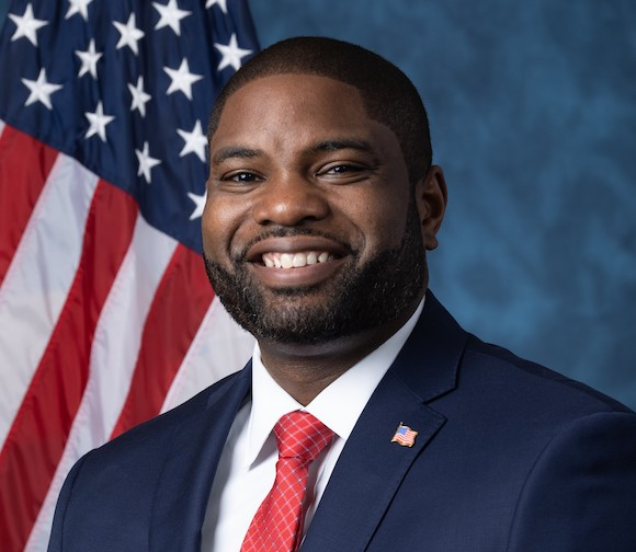 Possibly a future Republican in Congress Byron Donalds pictures in front of the american flag and a blue background while wearing a red tie and blue blazer