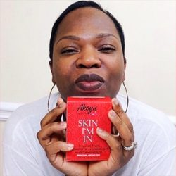 Nynoka Grant facing the camera in a white shirt while holding up the packaging for one of her products
