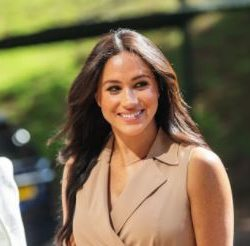 Meghan Markle smiling away from the camera wearing a tan sleeveless blazer