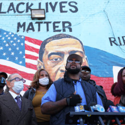 George Floyd painted mural and speakers talking to news stations on a podium