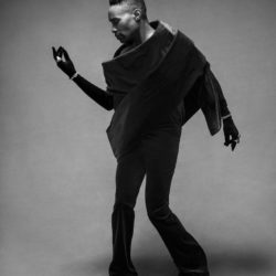 Billy Porter in a black and white photo posed to the side looking at his right hand