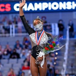 Simone Biles holding a bouquet of flowers after a gymnastics competition while waving at fans